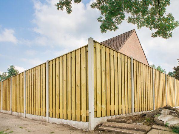 New wooden fence as corner around garden of home
